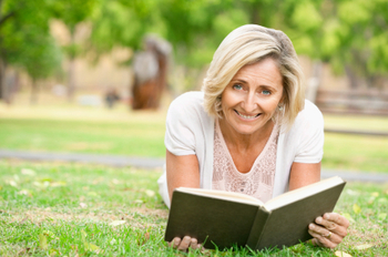Senior Woman Reading In The Grass