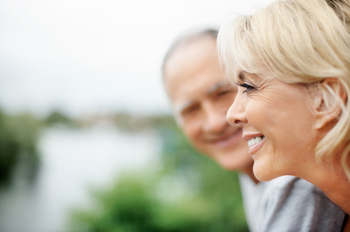 Happy mature woman with senior man in blur background